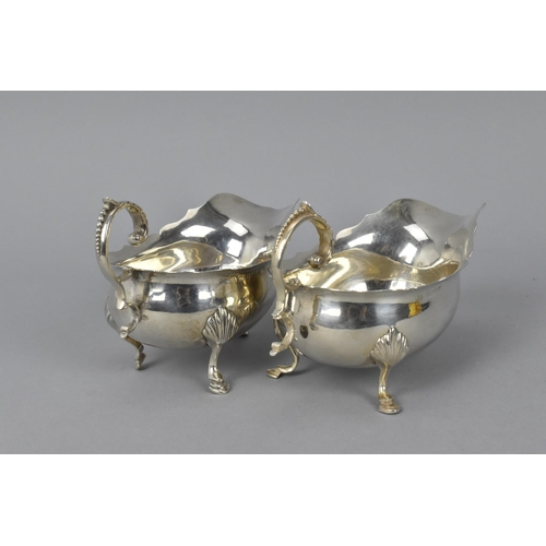 65 - A pair of Edwardian silver sauce boats by Charles Horner, Birmingham 1904, with c scroll handle, on ...