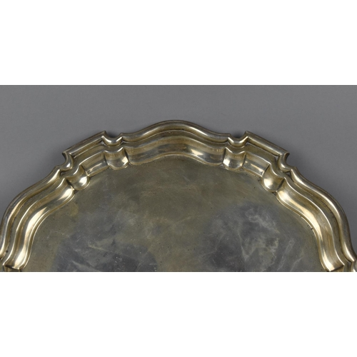 9 - A George V silver salver by Mappin & Webb, Sheffield 1917, with thick pie crust edge, supported on t...
