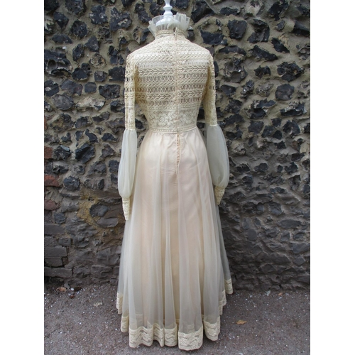 194 - A late 1960s/early 1970s Jean Varon cream chiffon evening dress with crochet lace bodice, cuffs and ...