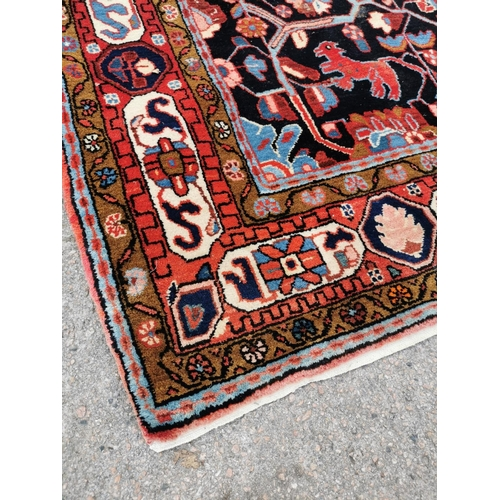 203 - A large hand woven Persian Heriz rug, with central blue ground medallion surrounded with doves, lotu...