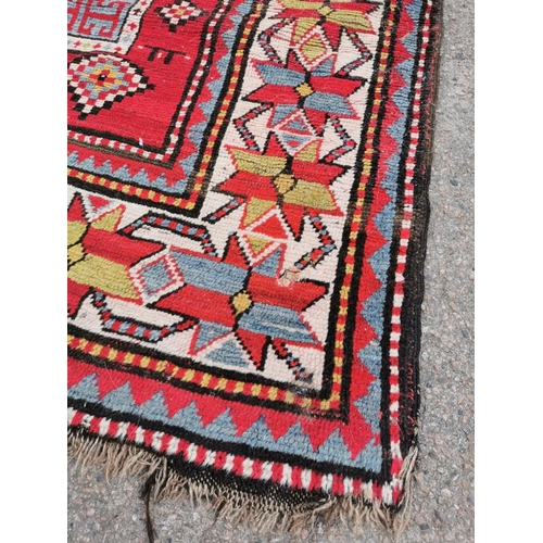 204 - Two tribal Caucasian hand woven rugs, possibly Karagashli, with geometric designs on red grounds, wi...