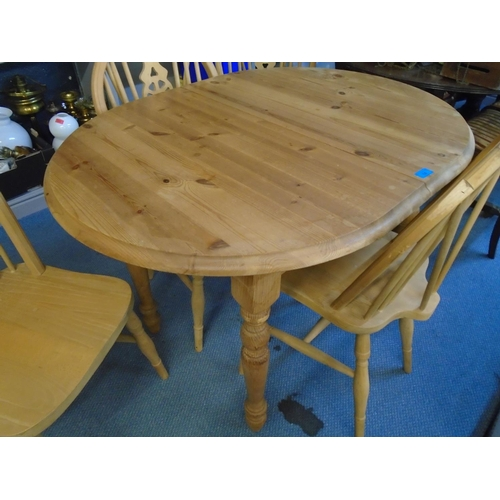 74 - A pine extending kitchen table with rise and fall leaf, and four winder wheel back style kitchen cha...