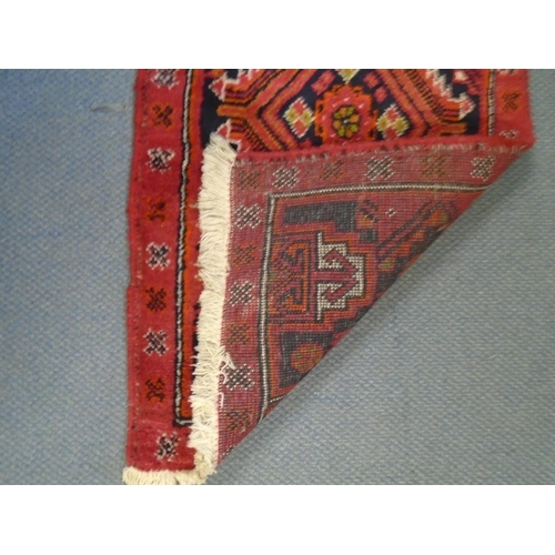 75 - A small handwoven Middle Eastern runner, red ground with a line of four elephant gulls, geometric an...