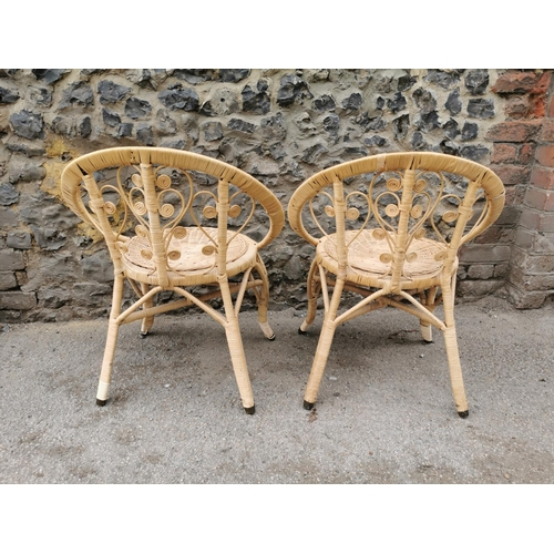 29 - A pair of rattan conservatory chairs, designed with stylised floral scrolls, circular wicker seat, h...