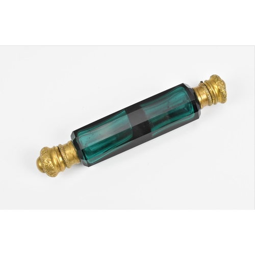 39 - A Victorian double ended glass scent bottle, the faceted green glass body mounted to either end with...