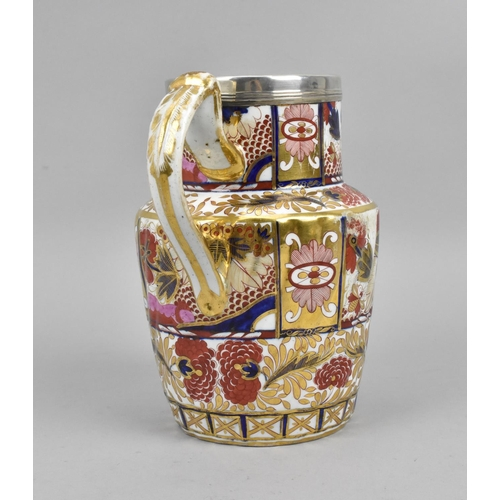 45 - A Victorian ironstone ceramic jug, with white metal mounted rim, designed with painted florals and g...