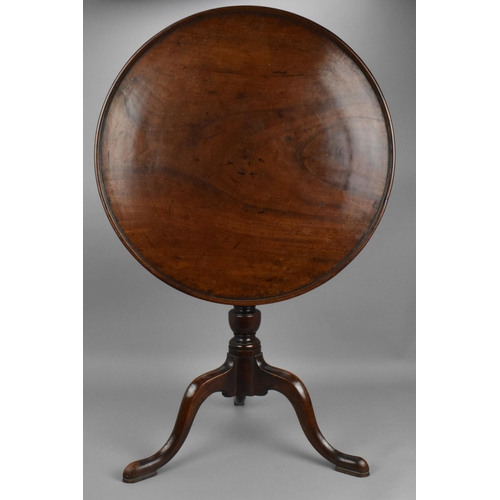 115 - A Georgian mahogany occasional table, the tilt top of circular form with moulded border, above a tur...