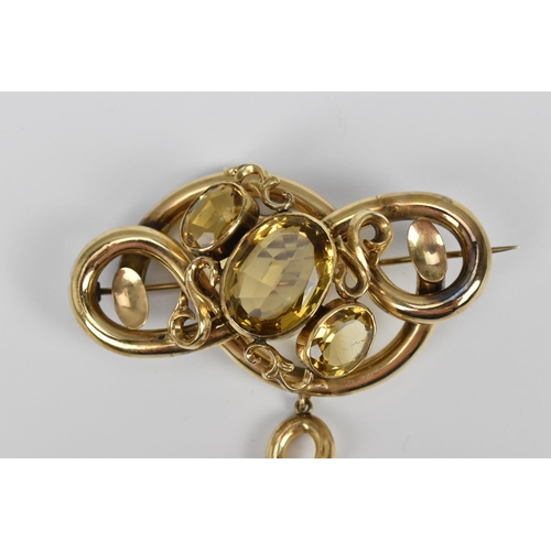 146 - A Victorian yellow metal and citrine brooch, designed with knotted gold and set with a central large...