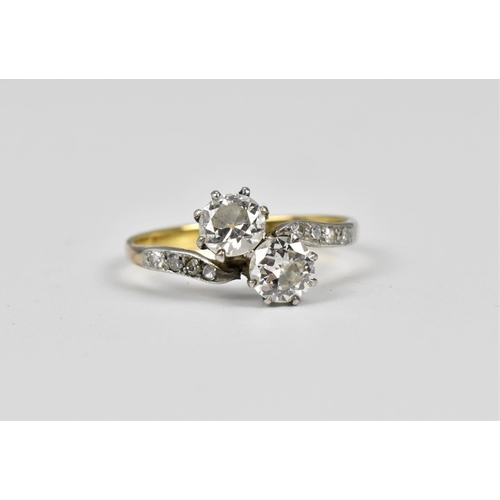 147 - An 18ct gold and diamond toi et moi ring, the two entwined round cut diamonds flanked with four diam...