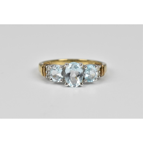 149 - An aquamarine and diamond set ring, with three central oval cut aquamarines flanked with two diamond...