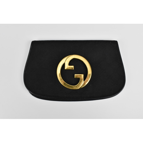 174 - A 1970's Gucci black monogrammed canvas Blondie clutch bag with large gold tone double G interlocked...