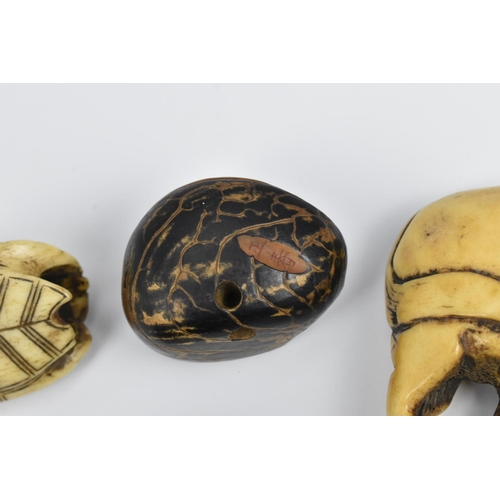 30 - A small group of Japanese carved netsukes, to include a carved wooden abalone shell, with textured d...