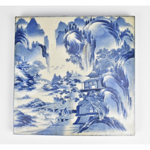 31 - A large Chinese Qing dynasty blue and white porcelain tile, 19th century, depicting mountains, river...