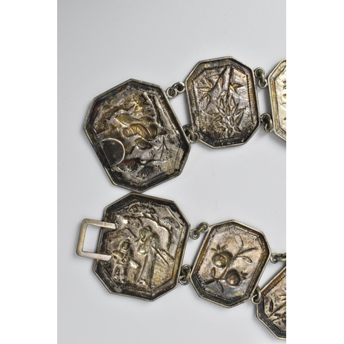 34 - A Chinese early 20th century white metal link belt, with seventeen embossed panels with floral desig...