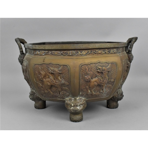 35 - A Chinese cast bronze twin handled jardinière pot, of octagonal form with bulbous body, each faceted...