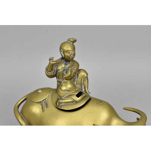 41 - A Chinese turn of the century brass model of a sage on a water buffalo, 22 cm high x 22 cm wide, tog...