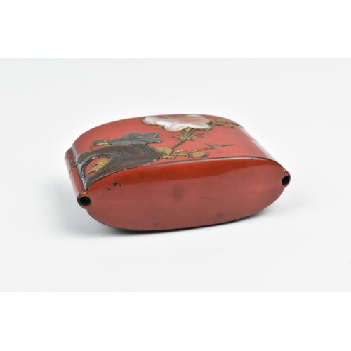 14 - A Japanese Meiji period red lacquer two case inro, decorated with relief flowers to one side and mac...