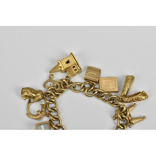 190 - A 9ct gold charm bracelet, the cable chain holding various miniature charms of buildings, animals, s...
