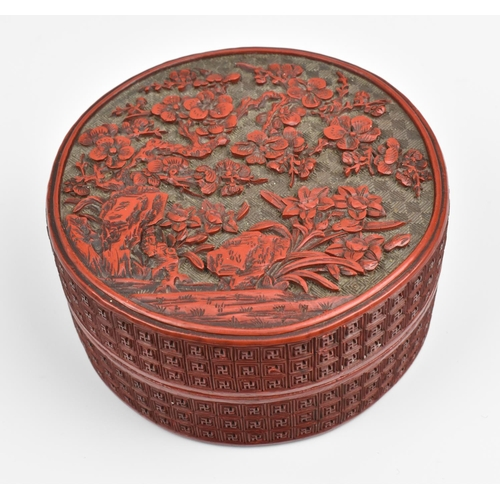 2 - A Chinese Qing dynasty carved cinnabar lacquer box, of cylindrical form, the lid with intricately de...