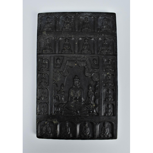 57 - A Chinese carved spinach jade tablet of Buddha, sat in a lotus position surrounded with his disciple...