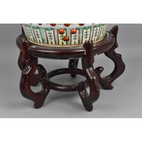 67 - A 20th century Chinese Famille Verte porcelain garden seat decorated with shaped panels of figures i...