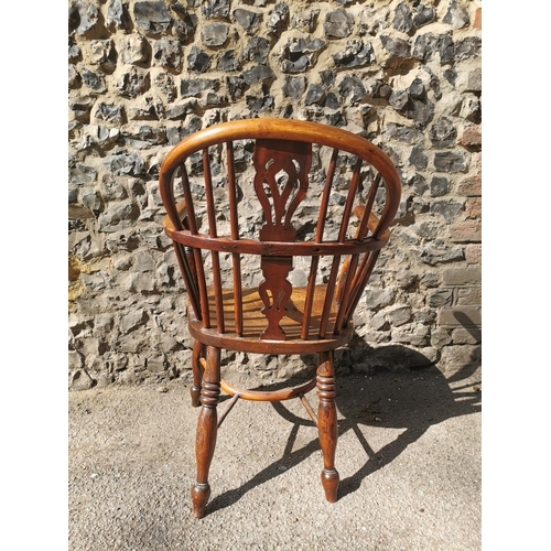 135 - A Georgian ash and elm comb back Windsor armchair with pierced central splat turned legs and crinoli...