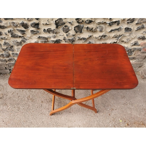 193 - A 19th century mahogany folding campaign or coaching table, raised on scissor action shaped x-frame ...