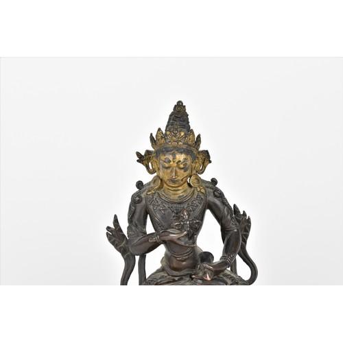 78 - A Sino-Tibetan bronzed copper alloy model of Tara Bodhisattva, sat in a lotus position holding a dor...