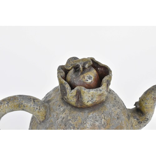 81 - A Chinese stoneware teapot of naturalistic form with ruched opening and lid mounted with an animal o...
