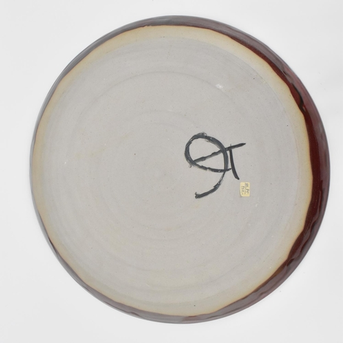 13 - A large Ruskin style sang de boeuf mottled glazed pottery charger by Tammy Josephson, of circular fo...