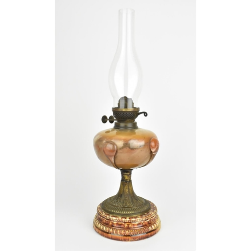 42 - A 19th century Arts and Crafts style oil lamp, with bulbous glass body on a spreading metal pedestal...