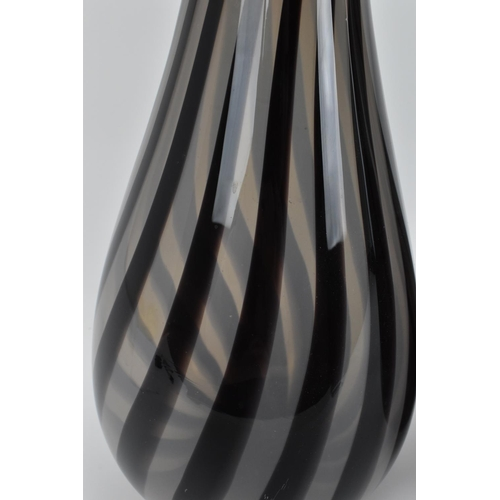 9 - Two hand blown Anthony Stern studio glass vases, of elongated form with bulbous base and twisted can...
