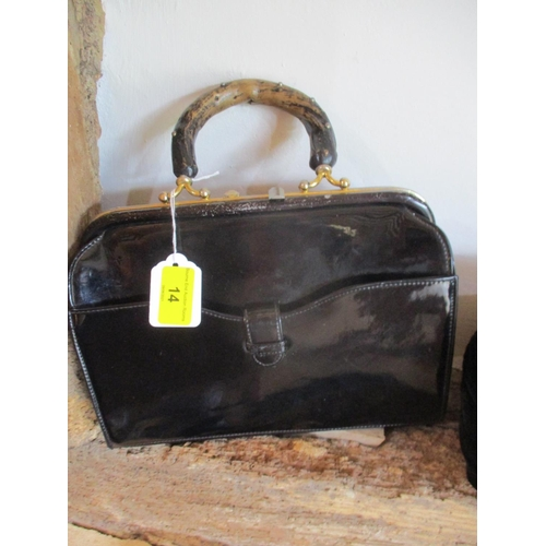 14 - Two mid 20th century handbags, one patent leather with a wooden handle and the other a cream Chamell...