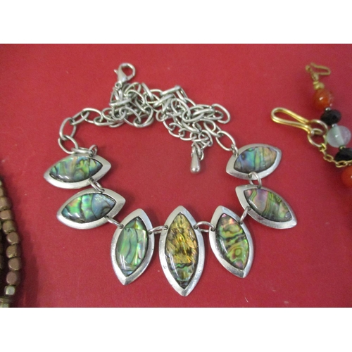 31 - A quantity of costume jewellery to include a long length of seed pearls and silver and abalone jewel...