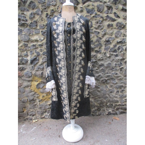 """A vintage S.B Watts Costumers theatrical costume in the style of a Louis XVI gentleman's costume in black with ornate needlework in gold metallic thread having lace cuffs and gold coloured buttons, comprising a knee length waistcoat and outer coat measurements 40"""" chest x 43"""" long Location: Rail"""
