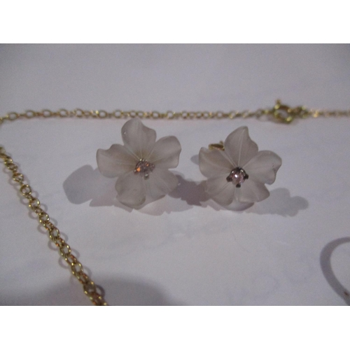 12 - A 9ct gold and frosted glass jewellery suite consisting of a three flower brooch, two pairs of earri...