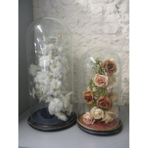 Two early 20th century domed displays, one in the form of a vase of flowers using feathers as petals and the other a silk flower display Location: LWB