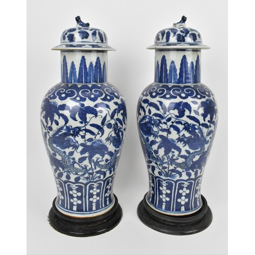 A pair of Chinese Qing dynasty blue and white porcelain lidded vases, 19th century, of baluster shape with Xuande style banding patterns to the collar and base, the body decorated with two four clawed imperial dragons, each 39 cm high x 20 cm diameter  Condition report: pitting to both vases, one vase with deep hairline cracks to the collar rim, the other with one hairline crack to collar rim, wear to bases commensurate with age, overall good