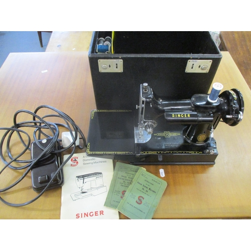 1 - A 1950s Singer 221k electric sewing machine, serial number EL213218, with foot pedal, manuals and ac...