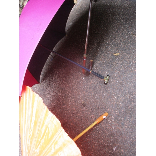 25 - A Giorgio Armani branded umbrella and another by Charles Jourdan, together with a burnt orange Orien...