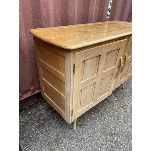 33 - A mid century Ercol light elm sideboard, with two carved doors enclosing two drawers and shelf space...