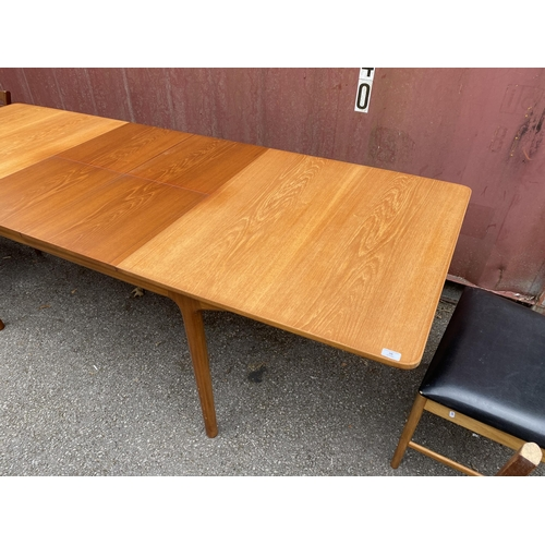 36 - A mid 20th century Alexander Henry McIntosh teak extending dining table and four chairs, two being c...