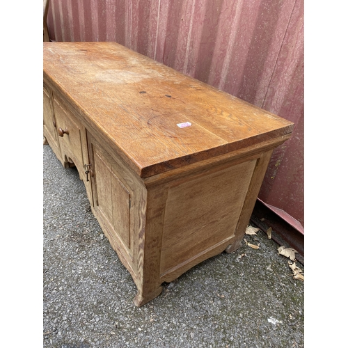 45 - Attributed to Heals a 1950s light oak low cabinet having a central door flanked by two cupboard door...