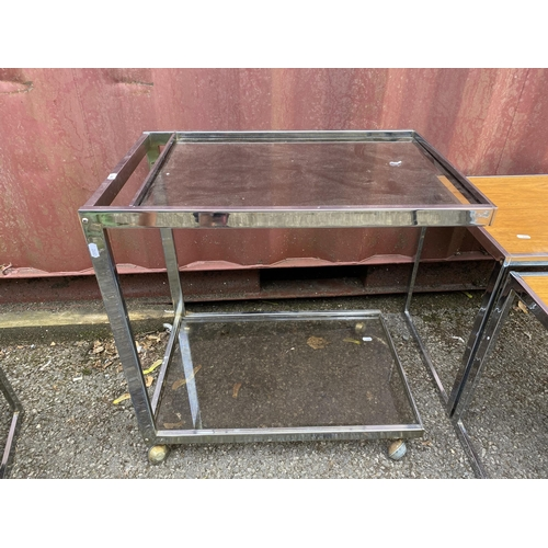56 - A nest of three Howard Miller for 'MDA' rectangular teak and chrome occasional tables, largest 48.5h...