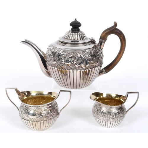 16 - A Victorian silver three piece tea service, with scrolling foliage border embossed bird heads, initi...