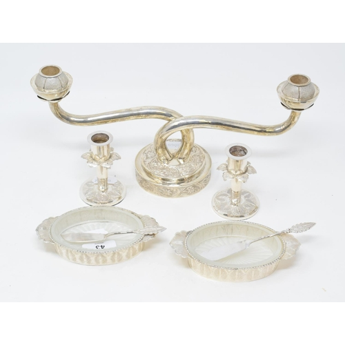 43 - An Eastern silver coloured metal two light candelabrum, 35 cm wide, a similar pair of dwarf candlest...