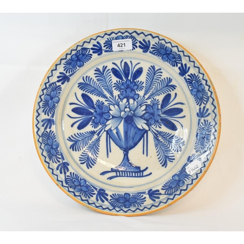 421 - A 19th century Dutch Delft plate, decorated a vase of flowers in underglaze blue, 35 cm diameter...