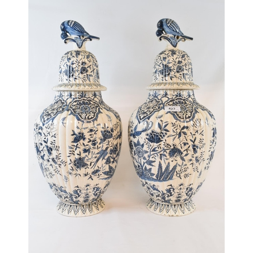 423 - A pair of Dutch Delft vases and covers, with bird finials, and decorated birds, flowers and foliage,...