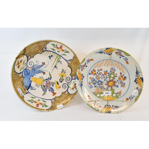 425 - A Dutch polychrome Delft plate, decorated a vase of flowers and a bird, 33.5 cm diameter, and anothe...