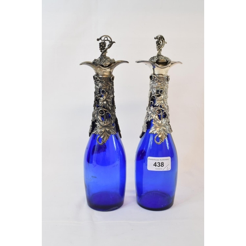 438 - A pair of blue glass decanters, with plated grape and vine mounts, 29 cm high (2)...